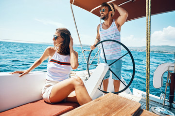 Young man and woman on a sailing boat -Romantic vacation and luxury travel..