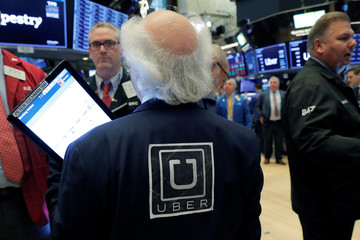 Trader wears Uber logo jacket as Uber Technologies Inc. holds IPO on floor of NYSE in New York
