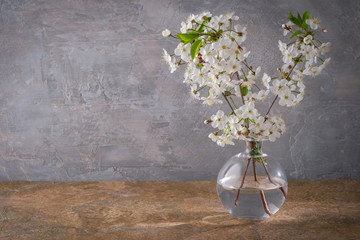 Foto op Canvas Lelie Cherry blossoms in a vase on a table.