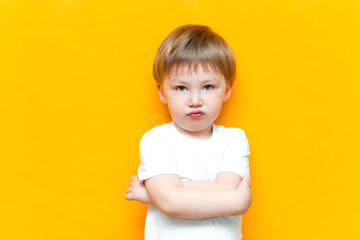 Portrait of angry little boy with arms folded isolated on yellow background. Sad and unhappy child. Upset toddler boy