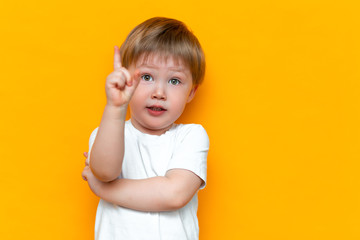 Portrait of cute handsome blonde little boy with finger pointed up. Little child has idea. Kid isolated on yellow blackground. Success, bright idea, creative ideas