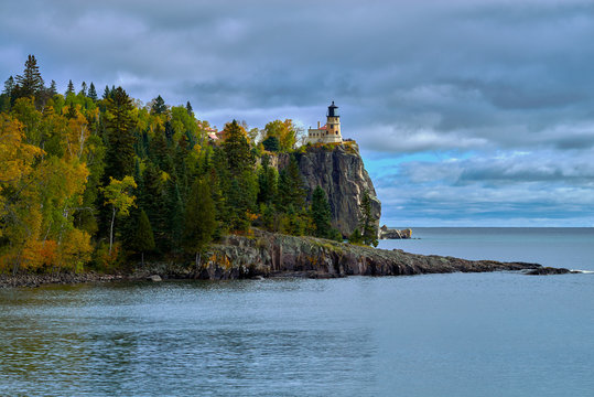 split rock lighthouse towers over lake superior, from its 165 foot cliff, in northeastern minnesota, early autumn.