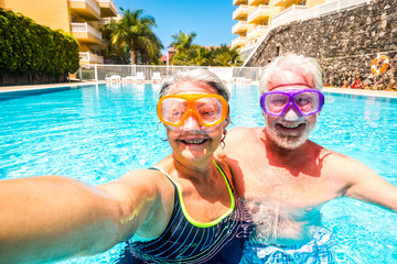 Happy cheerful people old senior man and woman have fun together in the summer swimming pool activity taking selfie pictures with scuba masks on the face for funny outdoor leisure activity in vacation Wall mural