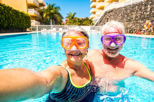 Happy cheerful people old senior man and woman have fun together in the summer swimming pool activity taking selfie pictures with scuba masks on the face for funny outdoor leisure activity in vacation