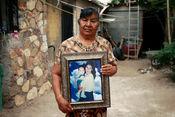 Maria del Carmen Vazquez poses for a picture as she holds a photograph of her daughter Esther Arredondo Vazquez, a migrant living in Canutillo, Texas, U.S., in Ciudad Juarez
