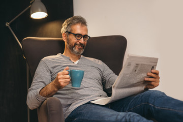 senior man reading newspaper and drinking tea relaxed in his sofa at home