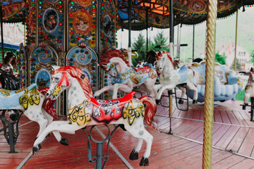 Multi-colored children's carousel with horses marry-go-round at the summer fair. Horizontal image.