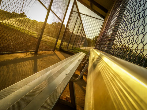 Angled Photo of a Baseball Dugout at Sunset - with Bleacher Seats, Chainlink Fences and Streaming Sprinklers in the Background