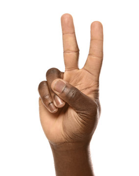 African-American man showing PEACE sign on white background, closeup