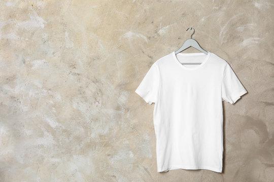 Hanger with white t-shirt on color background. Mockup for design