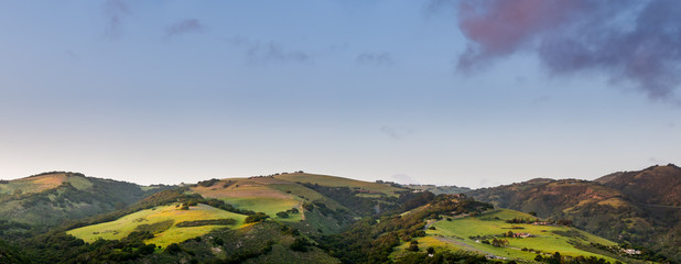 Panorama of beautiful green hills, mountains, and fields in sunset light under a blue sky with purple clouds in Carmel Valley, CA, USA