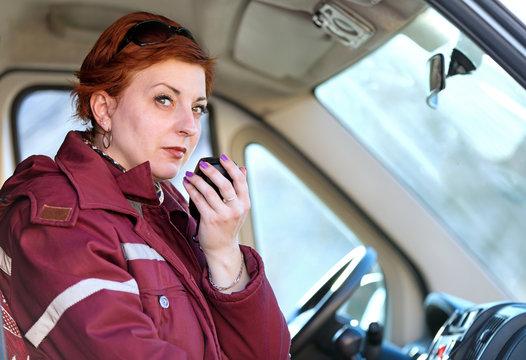 Emergency medical service. Female paramedic worker making EMS Radio Report while sitting in ambulance cab