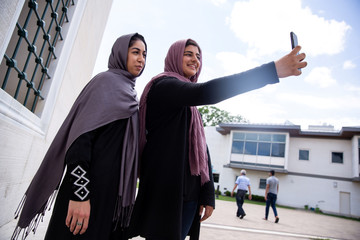 Two Muslim women take pictures after the first Friday prayers during the month of Ramadan at Diyanet Center of America in Lanham