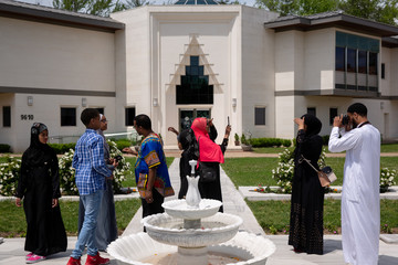 A Muslim family takes pictures ahead of the first Friday prayers during the month of Ramadan at Diyanet Center of America in Lanham