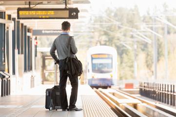 Businessman business traveler commuter with roller bag suitcase waiting on train station platform