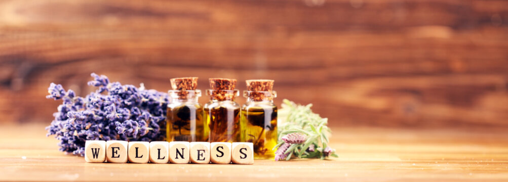 lavender oil in a glass bottle on a background of fresh flowers.