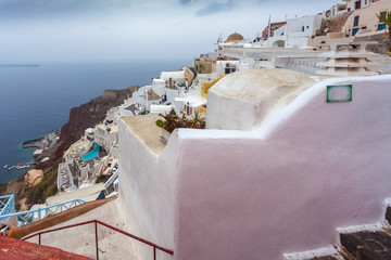 Panorama of white houses of Oia and red cliffs on rainy day