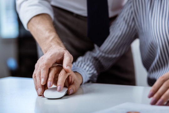 Woman with accurate manicure and striped shirt carrying white computer mouse