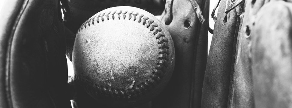 Close up of old vintage baseball in used worn leather glove, black and white sports banner.