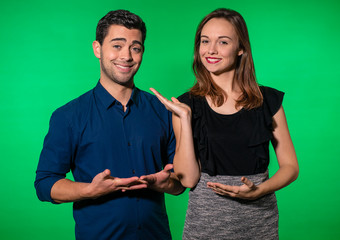 Cute, happy young couple (man and woman) standing in front of a greenscreen studio background