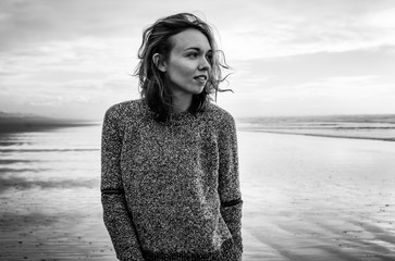 Black and white portrait of a young woman standing on a cold, windy beach in California