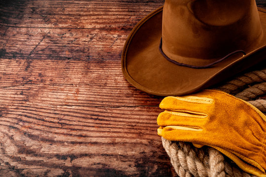 American culture, living on a ranch or farm and country muisc concept theme with a cowboy hat, rope lasso and rodeo leather gloves on a wooden background in a old saloon with copy space