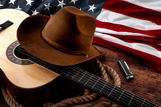 American culture, living on a ranch and country muisc concept theme with a cowboy hat, USA flag, acoustic guitar, harmonica and a rope lasso on a wooden background in a old saloon