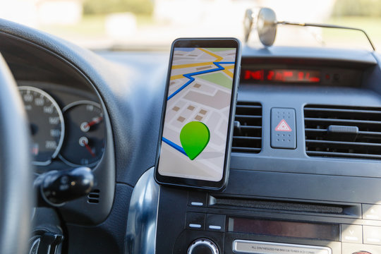 The map on the phone in the background of the dashboard. Black mobile phone with map gps navigation fixed in the mounting. App map for travel.