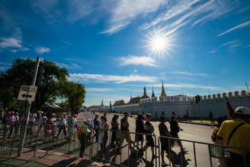 Wall Mural - Bangkok, Thailand - JANUARY 2, 2019: Crowd of tourists walking cross road to golden ancient temple at Wat Phra Kaew, Sightseeing attraction in Asia. Temple of the Emerald Buddha.