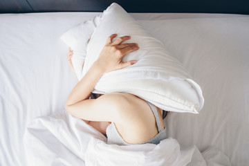 High angle view of young woman lying on bed and she hate to waking up in the early morning. Sleepy girl trying to hide under the pillow. Wall mural