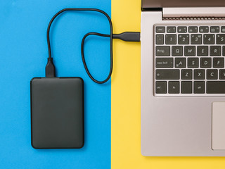 Black hard drive and laptop on yellow and blue background. Flat lay. The concept of backup storage.