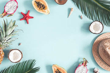 Summer composition. Tropical palm leaves, hat, fruits on blue background. Summer concept. Flat lay, top view, copy space Wall mural