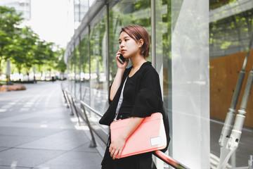 パソコンケースを持ちながらスマートフォンで電話する女性