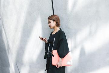 パソコンケースを持ちながらスマートフォンを使う女性