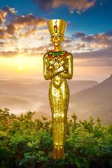 Nofretete, Statuette goldfarben vor schönem Hintergrund mit Sonnenaufgang, ägyptischer Pharaon und Göttin