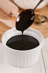 Blackstrap molasses or treacle a viscous dark sugar syrup produced from sugar cane and used as a sweetener in baking and cooking