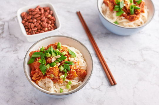 shan noodles with peanuts and chopsticks at white marble tabletop. burmese cuisine traditional dish. myanmar food. rice noodles with pork in tomatoes. copy space.