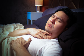 asian man has a heart attack symptoms and breathing problem while sleeping on bed at night
