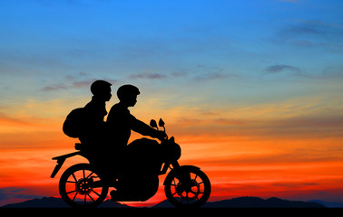 silhouette of lover couple in sunset with classic motorcycle
