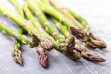 Fresh raw garden asparagus closeup on concrete gray background. Spring seasonal vegetables. Low shallow focus