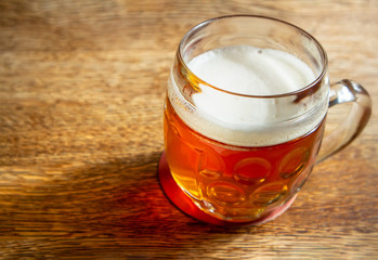 Glass mug of beer on a wooden table in natural sunlight. Low shallow focus