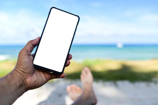 Men hand holding a white screen blank phone.He slept on the beach.