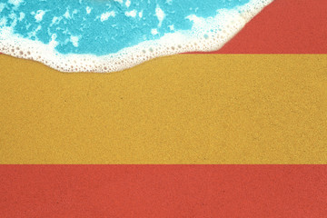 Sea wave on the sunny sandy beach with flag Spain. View from top on surf.