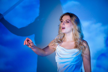 The blonde girl singer in a white dress on a blue background in a studio.