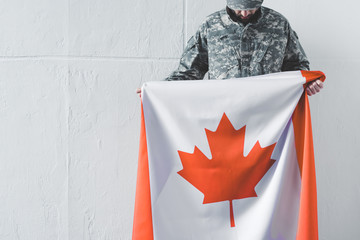 man in military uniform holding canada national flag while standing near white wall with bowed head