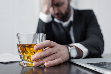 In de dag Alcohol selective focus of depressed businessman holding glass of whiskey