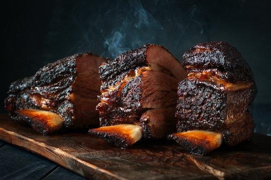 A large steaming fragrant piece of baked beef brisket on the ribs with a dark crust. Classic Texas barbecue