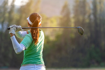 Sport Healthy. Asian sporty woman golf player doing golf swing tee off on the green sunset evening time, she presumably does exercise. Healthy and Lifestyle Concept.