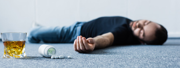 panoramic shot of unconscious man lying on grey floor near glass of whiskey and container with pills