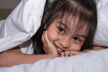 cute little girl on the bed woke up in the morning in her bed. soft white bed for a child, hiding under the blanket